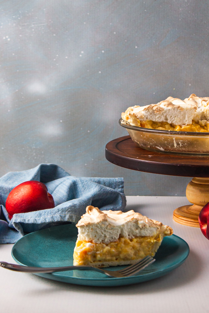Slice of stone fruit pie with remainder in pan on stand