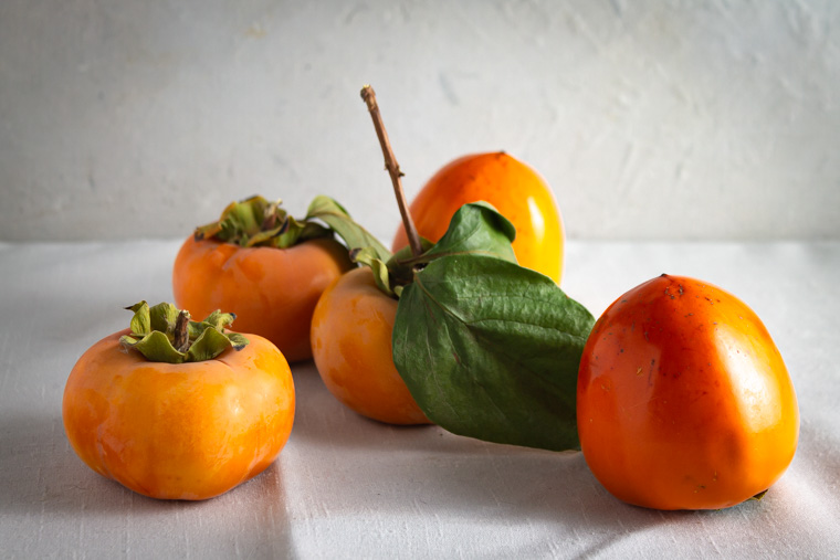 Fuyu and hachiya persimmons on a white background