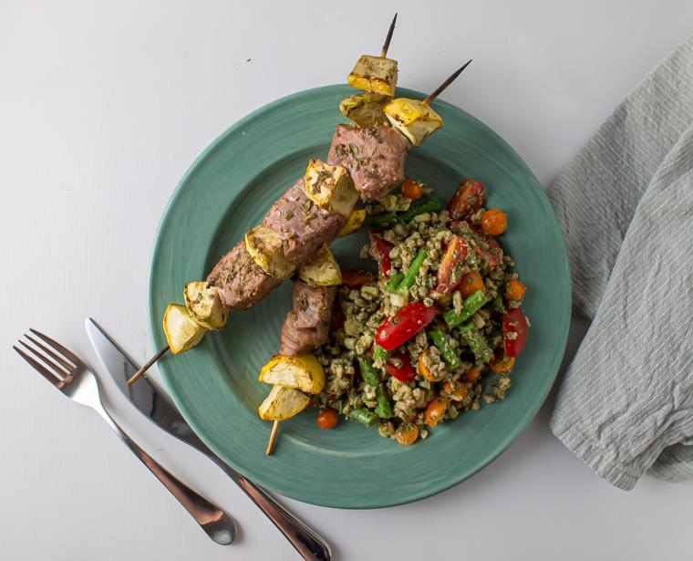 Plate with lime coriander tuna skewers and sage pesto farro salad