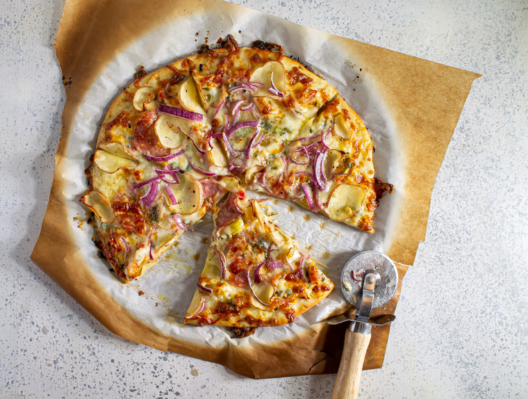 Pizza with red onion, potato, salami, and blue cheese