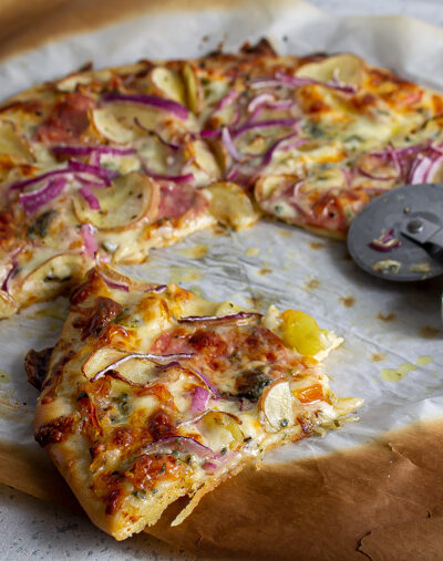 Pizza with potato, onion, and salami on a thin and chewy pizza crust