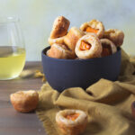 Glass of white wine paired with bowl of tapioca cheesee bread with butternut
