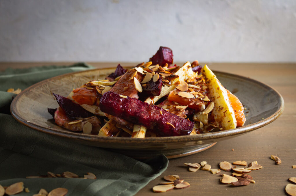 Roasted beets and parsnips with caracar oranges in a brown bowl on wood