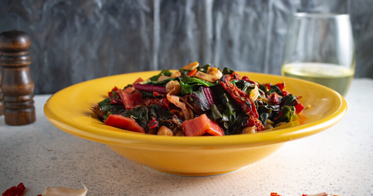 Yellow bowl with sauteed chard and chickpeas with glass of wine and pepper shaker