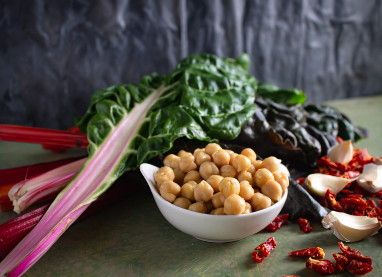 Ingredients: chard, chick peas, sun-dried tomato, and garlic on green background
