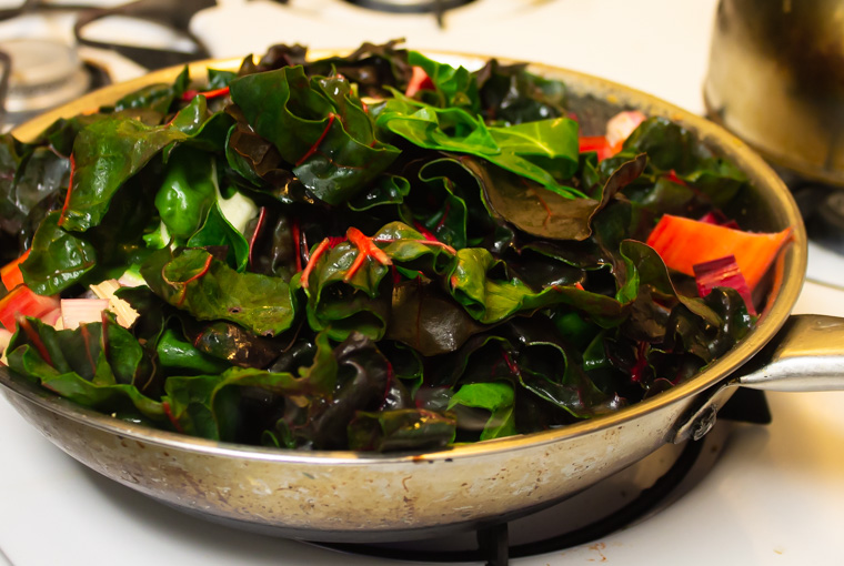 Chard being added to frying pan