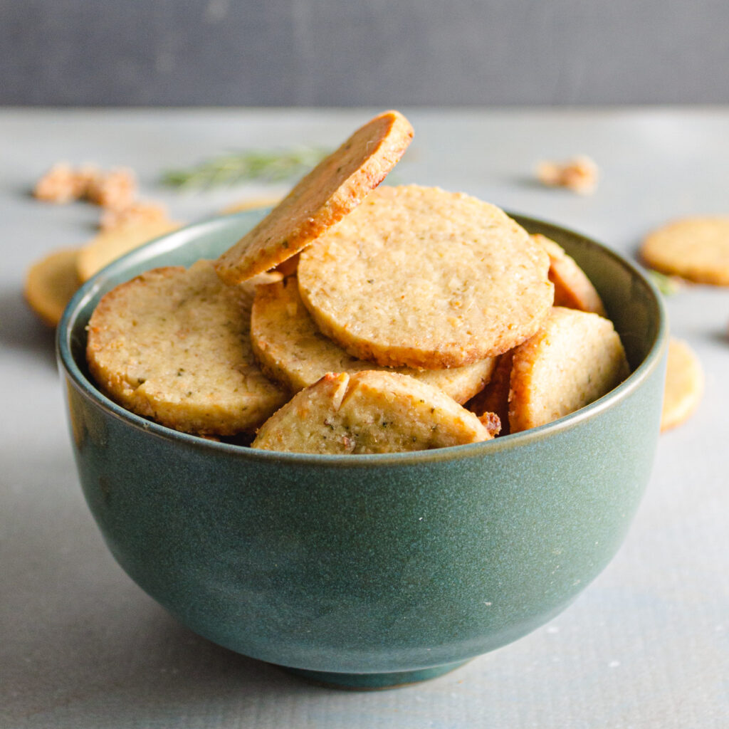 Teal bowl of gorgonzola walnut cookies on a blue background