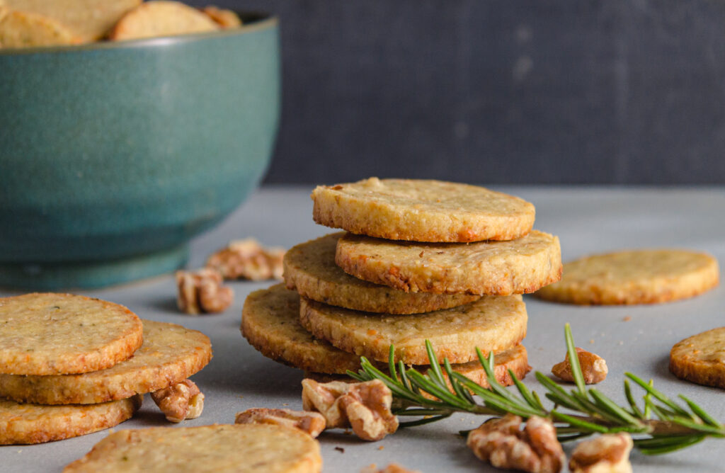 A stack of gorgonzola walnut cookies with rosemary and walnuts and a blue bowl in the background.